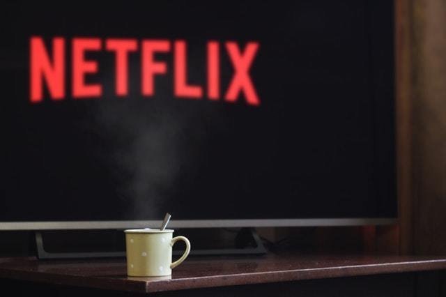 A TV showing Netflix on the screen with a cup sitting on a table in front of it