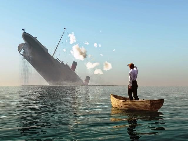 A man standing in a boat watching a ship sink